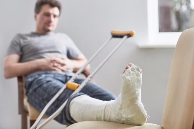 Zbliżenie na gipsową nogę młodego mężczyzny i po kontuzji biegania lub upadku.