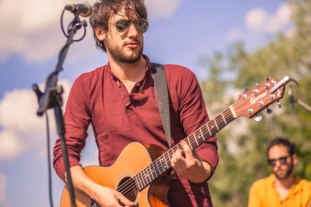 Zbliżenie na gitarzystę grającego na swoim instrumencie na koncercie