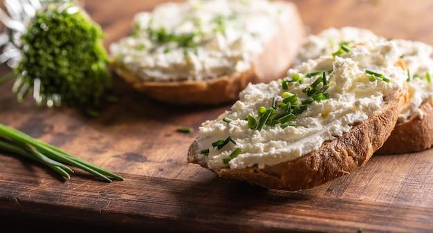 Zbliżenie na grubą pastę z owczego sera na kromkach chleba z drobno posiekanym szczypiorkiem na wierzchu.