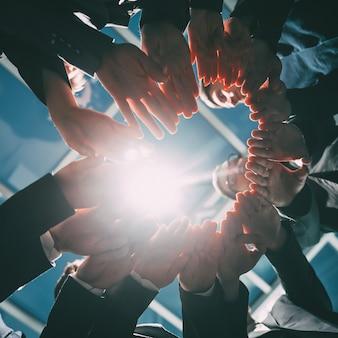 Zbliżenie na grupę młodych ludzi biznesu łączących się w dłonie