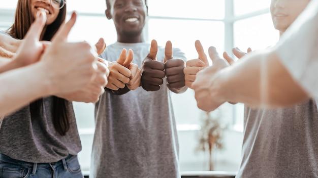 Zbliżenie na grupę młodzieży stojącej w kręgu i pokazującej kciuk w górę