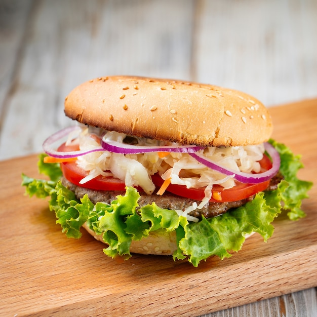 Zbliżenie na hamburger z kapustą i sałatą na drewnianej desce