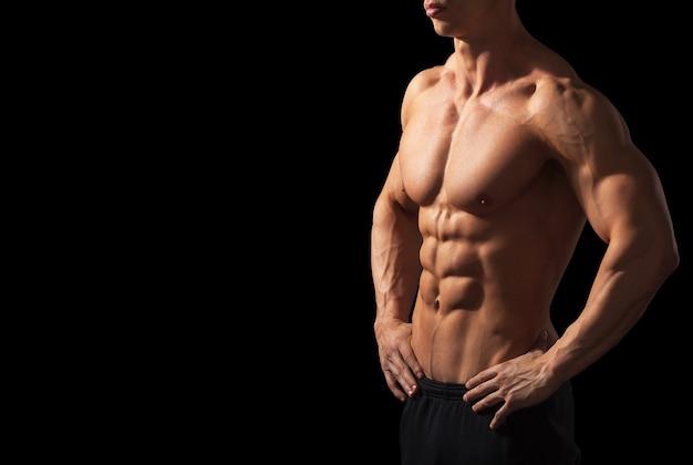 Zbliżenie na idealne męskie ciało na białym tle na czarnym tle z miejscem na kopię