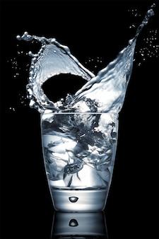 Zbliżenie na imponujący plusk wody w szklanym kubku na czarnym tle