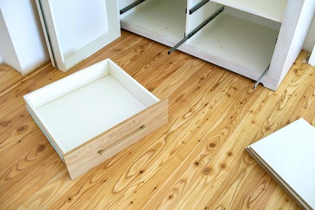 Zbliżenie na instalację drewnianej szuflady we współczesnej szafce.
