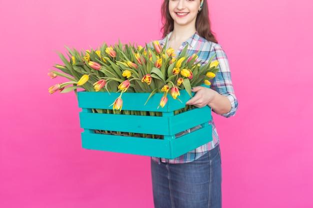 Zbliżenie na jasne drewniane pudełko z żółtymi tulipanami w różowym studio