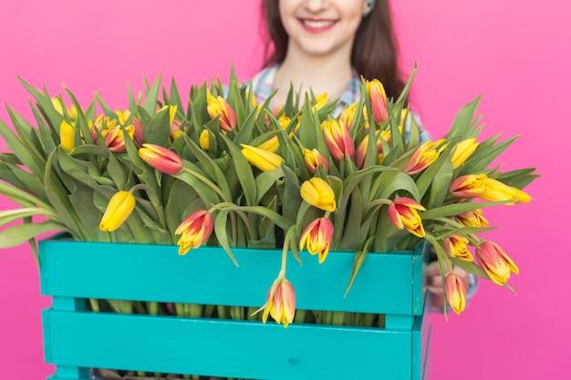 Zbliżenie na jasne drewniane pudełko z żółtymi tulipanami.