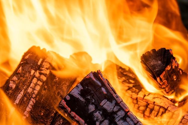 Zbliżenie na jasno płonące drewniane kłody z żółtymi gorącymi płomieniami ognia w nocy.