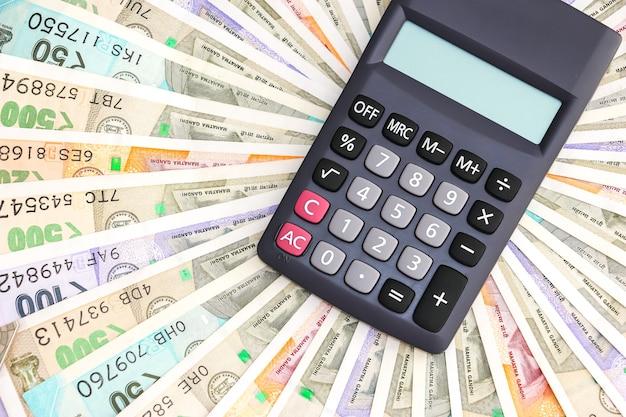Zbliżenie na kalkulator nad zupełnie nowymi indyjskimi banknotami 10 50 100 200 500 i 2000 rupii