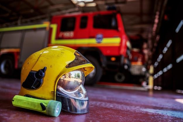 Zbliżenie na kask ochronny. w tle jest wóz strażacki. wnętrze straży pożarnej.