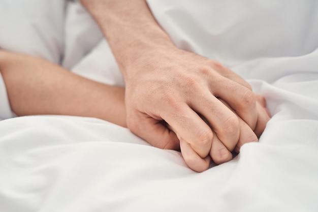 Zbliżenie na kaukaskiego mężczyznę i kobietę ze splecionymi palcami uprawiającymi miłość w łóżku