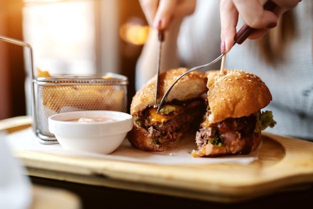 Zbliżenie na kaukaskiej kobiety jedzenie pysznego burgera siedząc w restauracji.