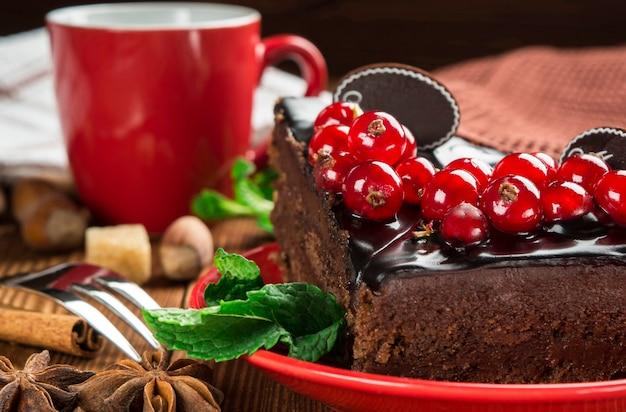 Zbliżenie na kawałek ciasta czekoladowego ozdobione czerwonymi porzeczkami na tle czerwonej filiżanki