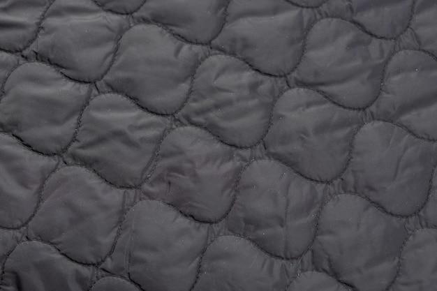 Zbliżenie na kawałek pikowanej tkaniny, podszewkę kurtki.