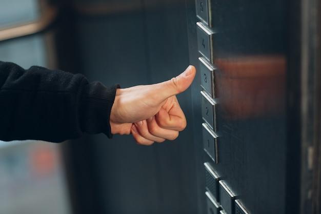 Zbliżenie na kciuki w górę, wciskające przycisk windy podczas pandemii koronawirusa covid-19.