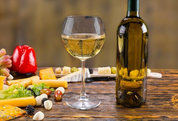 Zbliżenie na kieliszek białego wina z butelką na rustykalnym drewnianym stole w otoczeniu różnych serów i świeżych owoców