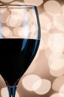 Zbliżenie na kieliszek czerwonego wina na tle lampek choinkowych.