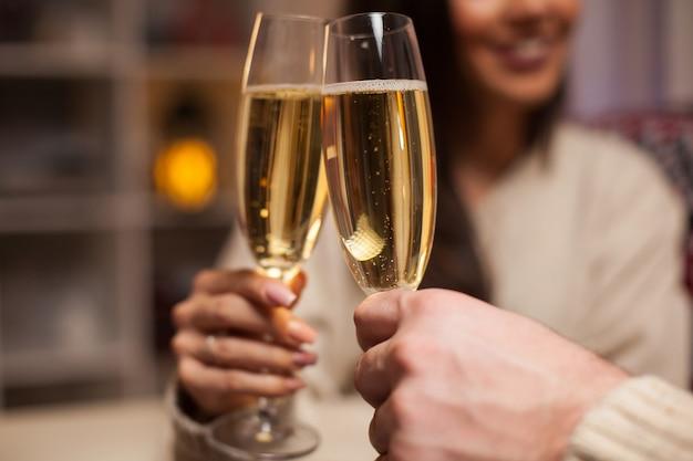 Zbliżenie na kieliszki do szampana trzymane przez wesołą parę świętującą boże narodzenie.
