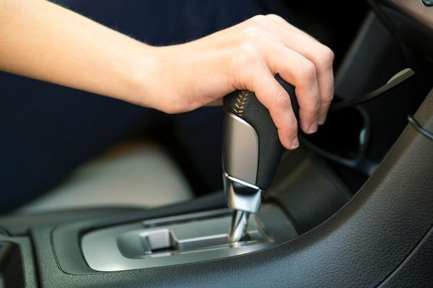 Zbliżenie na kierowcę kobieta, trzymając ją za rękę na drążek automatycznej zmiany biegów jazdy jako samochód.