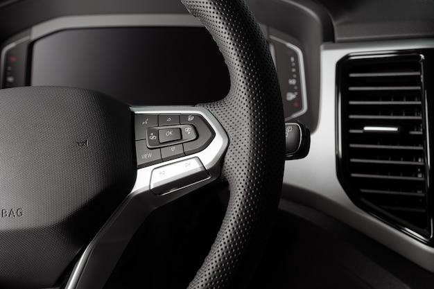 Zbliżenie na kierownicę nowego pojazdu, wnętrze kokpitu, elektryczne przyciski, cyfrowy prędkościomierz