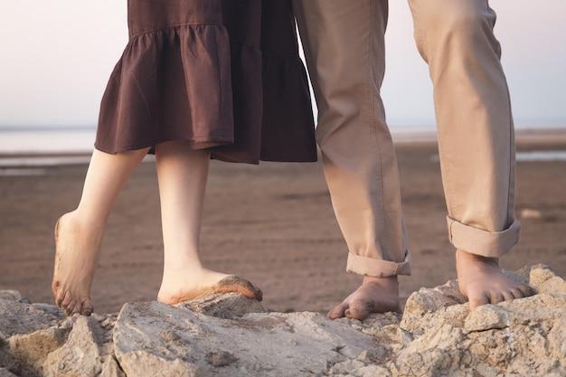Zbliżenie na kilka nóg na piaszczystej plaży.