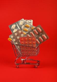 Zbliżenie na kilka różnych blistrów tabletek w małym koszyku na czerwonym tle, koncepcja dostawy zamówienia leków online, niski kąt widzenia