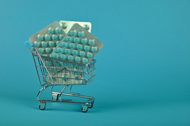 Zbliżenie na kilka różnych blistrów tabletek w małym koszyku na niebieskim tle, koncepcja dostawy zamówienia leków online, niski kąt widzenia