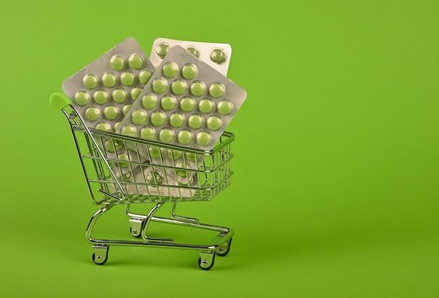 Zbliżenie na kilka różnych blistrów tabletek w małym koszyku na zielonym tle, koncepcja dostawy zamówienia leków online, niski kąt widzenia