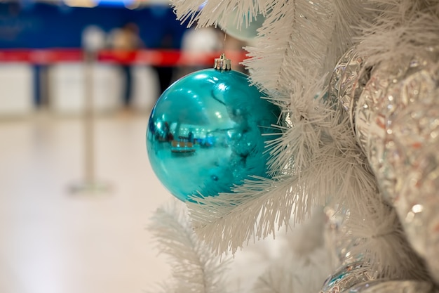 Zbliżenie na klasyczną niebieską piłkę na gałęzi jodły białej fragmentu nowego roku i choinki