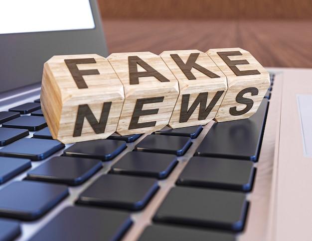 Zbliżenie na klawiaturę laptopa z drewnianymi kostkami i fałszywe wiadomości