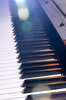 Zbliżenie na klawiaturę pianina elektronicznego w pięknym oświetleniu.