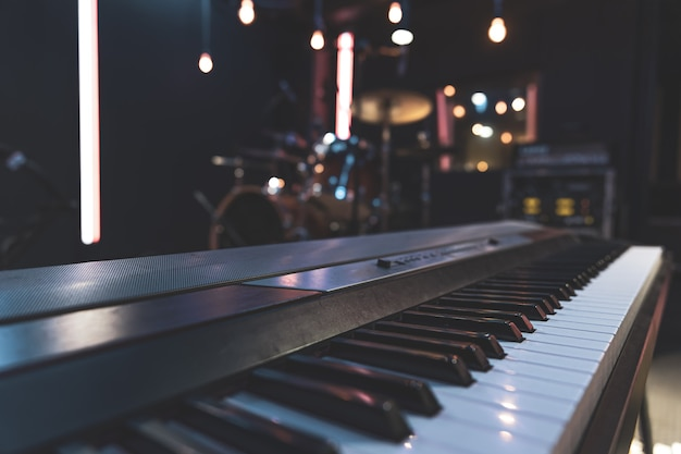Zbliżenie na klawisze fortepianu na niewyraźne tło z bokeh.
