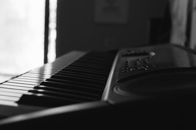 Zbliżenie na klawisze klawiatury elektronicznej fortepianu ze światłem słonecznym wpadającym przez okno