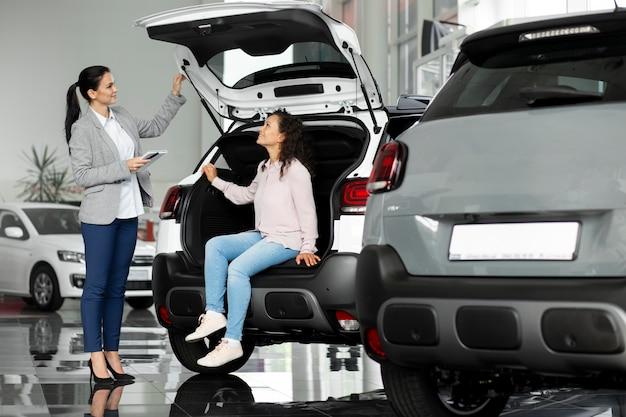 Zbliżenie na klienta z osobą biznesową w salonie samochodowym