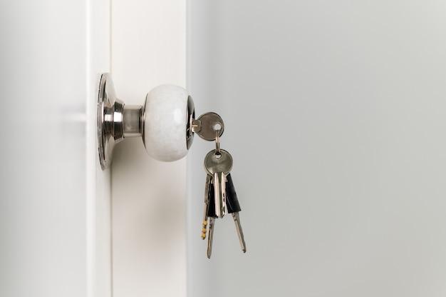 Zbliżenie na klucze w drzwiach zwisających z klamki na klucze w domu