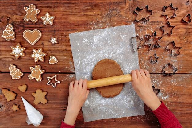 Zbliżenie na kobiece dłonie robiące imbirowe ciasteczka z ciasta w domu na święta bożego narodzenia