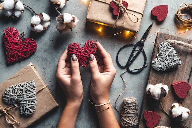 Zbliżenie na kobiece dłonie trzymające prezent w różowym sercu przedstawia na walentynki, urodziny, dzień matki. leżał na płasko. symbol miłości. walentynki tło z pudełka na betonowej desce.