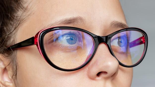 Zbliżenie na kobiece oczy w kobiecych okularach do pracy przy komputerze z niebieskimi soczewkami z filtrem