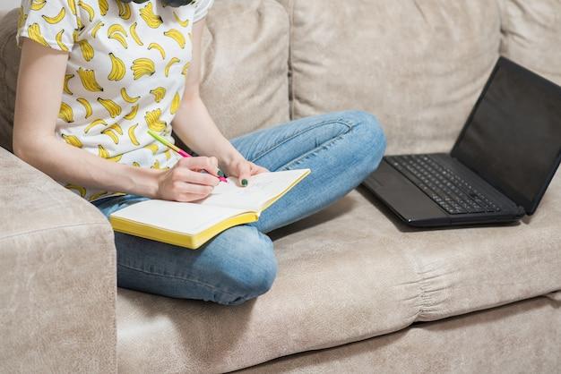 Zbliżenie na kobiece ręce, które piszą w zeszycie. praca w domu
