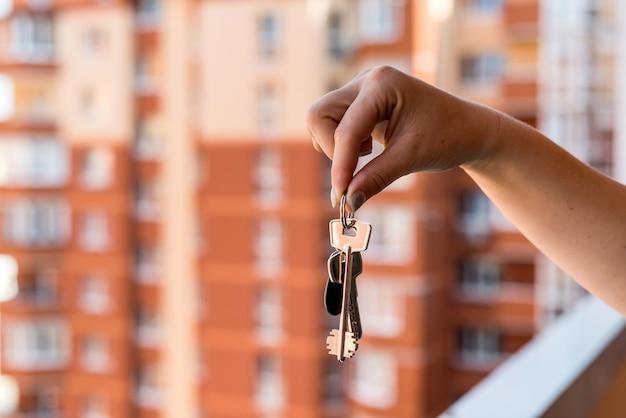 Zbliżenie na kobiecej dłoni z kluczami z nowego mieszkania