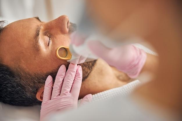 Zbliżenie na kobietę kosmetologa w sterylnych rękawiczkach usuwającą niechciane włosy z męskiego policzka za pomocą urządzenia laserowego