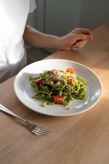 Zbliżenie na kobietę makaron fettuccine z sosem pesto na obiad, siedząc na stole w domowej kuchni.