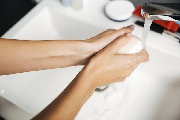 Zbliżenie na kobietę mycia rąk mydłem nad zlewem