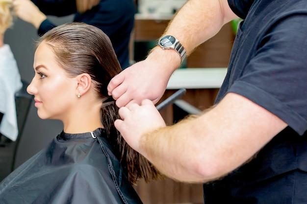 Zbliżenie na kobietę otrzymującą strzyżenie przez fryzjera w salonie fryzjerskim.