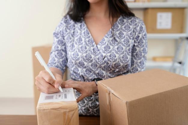 Zbliżenie na kobietę piszącą szczegóły na pudełkach dostawy