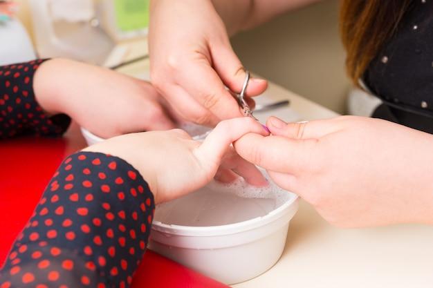 Zbliżenie na kobietę robiącą manicure - estetyczne przycinanie skórek małymi nożyczkami nad naczyniem z roztworem do namaczania w salonie spa