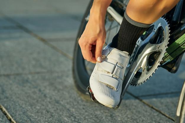 Zbliżenie na kobietę rowerzystę noszącą mocowanie butów rowerowych podczas jazdy na rowerze na świeżym powietrzu