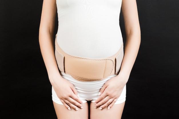 Zbliżenie na kobietę w ciąży z bandażem podtrzymującym na ból pleców na czarno
