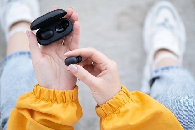 Zbliżenie Na Kobietę Wyjmującą Czarną Bezprzewodową Słuchawkę Douszną Z ładowarki. Kobiece Ręce Dotykając Przenośny Gadżet Słuchawki. Premium Zdjęcia