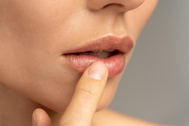 Zbliżenie na kobiety nakładające palcem nawilżający balsam odżywczy na usta